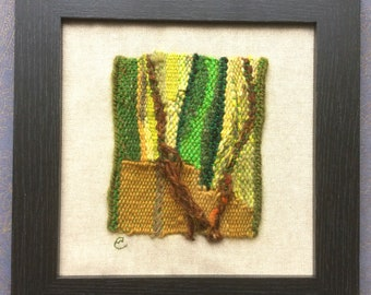 yellow framed tapestry weaving in shades of black For charity gold and pink,
