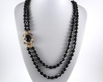 Black statement necklace with a decorative brooch style side clasp, bead necklace, costume jewellery, evening necklace.