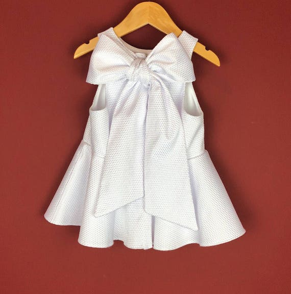 """The """"Bow-Backed Peplum"""" in White Pique."""