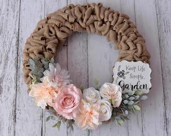 Burlap Wreath with pink and cream flowers and a vintage rustic sign