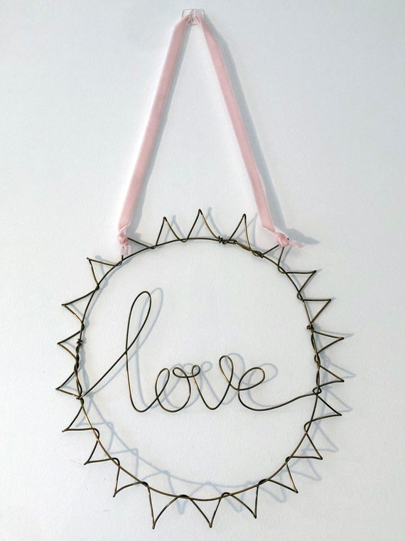Handwritten font 'Love', framed in a wire sun, hung with ribbon.
