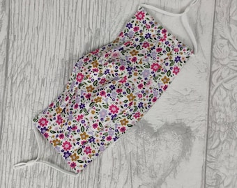 Face mask in pink and white flowery cotton. Hand made with three layers and is adjustable and washable. Ties behind ears or behind head.