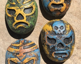 Four lucha libre cement mask magnets hand stained by Concrete Collectibles