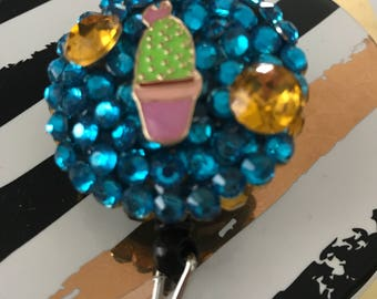 Cactus hand-made badge reel, Featuring teal and gold-like gems with a cactus on top.