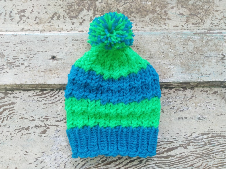 d9eb72981fd Knitted blue and green beanie hat with fluffy pom pom. Winter