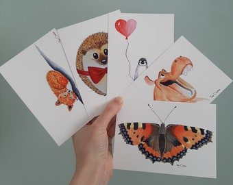 5 postcards with prints of watercolour illustrations of a hippopotamus, hedgehog, fox, butterfly and penguin.