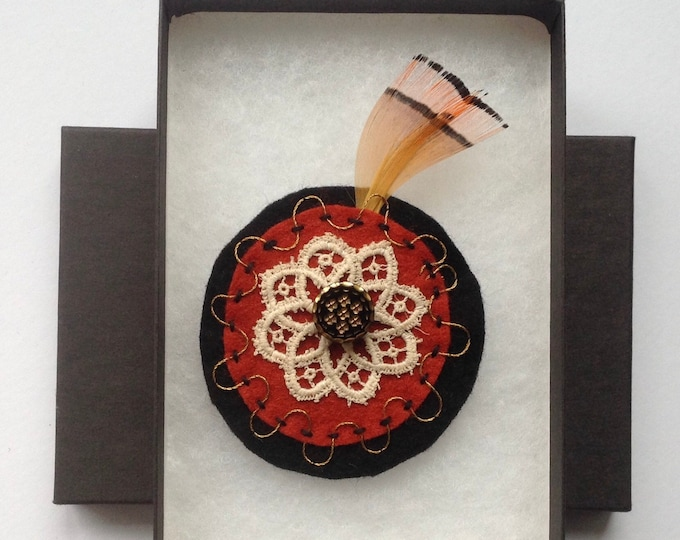 Hand embroidered, gold thread with vintage lace. Black and burnt orange felt, vintage button and feather corsage.