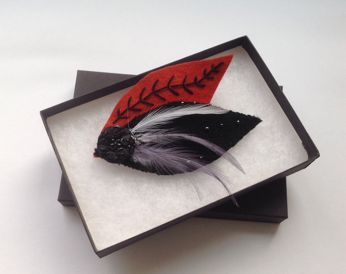 Black jet button corsage. Hand embroidered with beads and silver grey feathers. Black and red brick coloured felt shaped as leaves.
