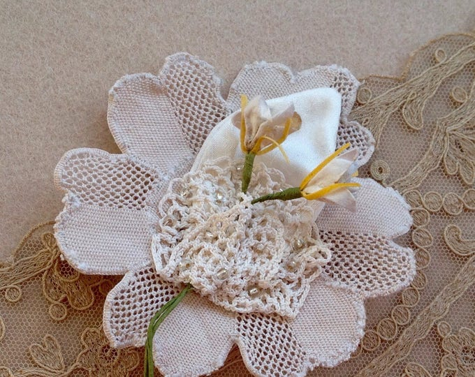 Flower corsage in antique lace, silk embroidered with glass beads.