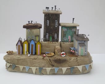 driftwood harbour scene with bathing huts, steps and bunting.