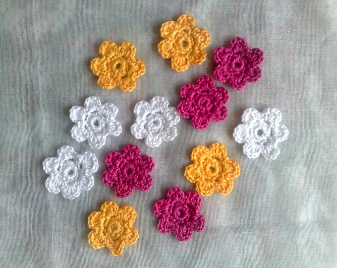 Colorful crochet flowers crocheted patch blossoms in the colors white, yellow and dark pink
