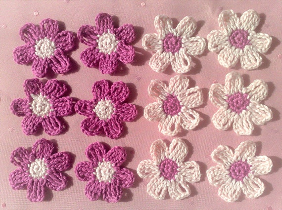 Small crocheted flowers in light pink and dark pink