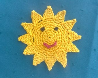 Crochet sun with a funny face for children's birthday decoration