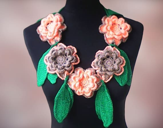 Crochet floral necklace with large 3D flowers in orange and grey and green leaves