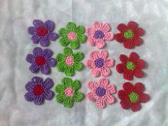 12 colorful crochet flowers in the colors green, lilac, pink and red