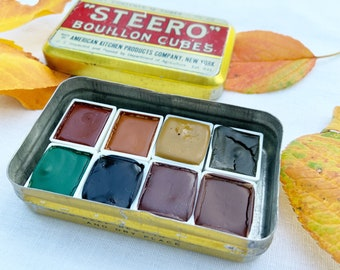 The Autumn Mountains Palette, a handmade watercolor set featuring 8 half pans in a vintage tin