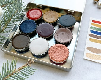 The Winter Cabin Deluxe Palette, a palette of 9 colors of handmade watercolor paint in a new tin