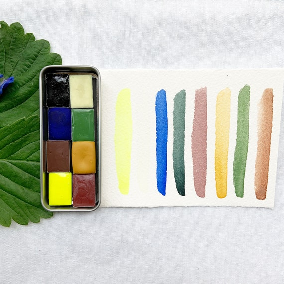 The Firefly Palette, a set of 8 colors of handmade watercolor paint in a new tin