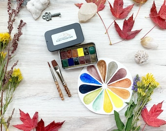 The September Sketcher's Palette, a set of 12 mini pans of handmade watercolor paint in a black matte tin