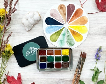 The Autumn Hills Palette, a set of 12 colors of handmade watercolor paint in a black matte tin