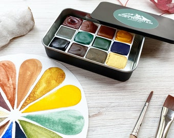 The Morning Sun Palette, a set of 12 colors of handmade watercolor paint in a black matte tin