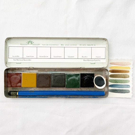 The Mountain Sketch Set, a set of 7 colors of handmade watercolor paint in a vintage tin