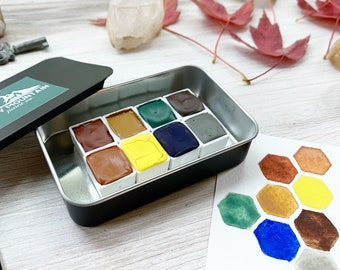 The Autumn Prairie Palette, a set of 8 colors of handmade watercolor paint in a black matte tin