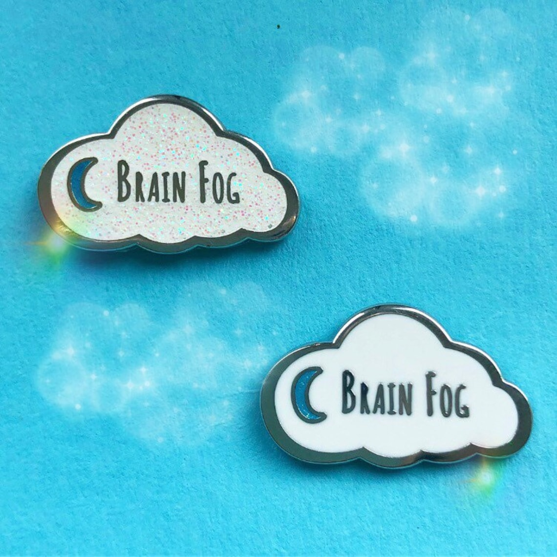 """Two cloud-shaped pins with a moon symbol and the words """"Brain Fog."""" One pin is glittery and one is not."""