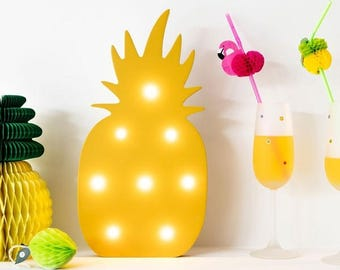 Led lamp in the shape of a yellow pineapple. Spreading a beautiful and relaxed light, designing a tropical dessert table or designing.
