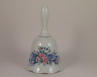 Vintage porcelain hand bell 1988... Albert E Price company...Made in Taiwan... Clapper... Flower with ribbon motif