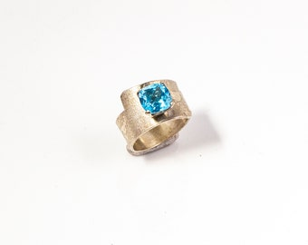 Ring in sterling silver and wrap-over design with cushion blue topaz faceted precious stone