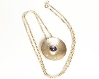 Pendant in sterling silver with moonscape finish and iolite cabochon on a box chain.