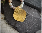 18ct yellow gold and diamond pendant on an 18 inch fresh water pastel pearl necklace with 18ct yellow gold lobster clasp.