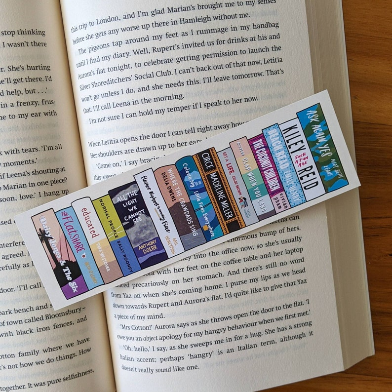 Bookmark depicting the spines of 15 popular books on bookstagram, photographed on an open book