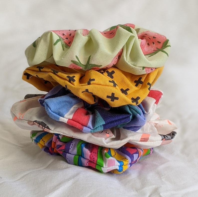 5 colourful scrunchies with various patterns, photographed on a white sheet background