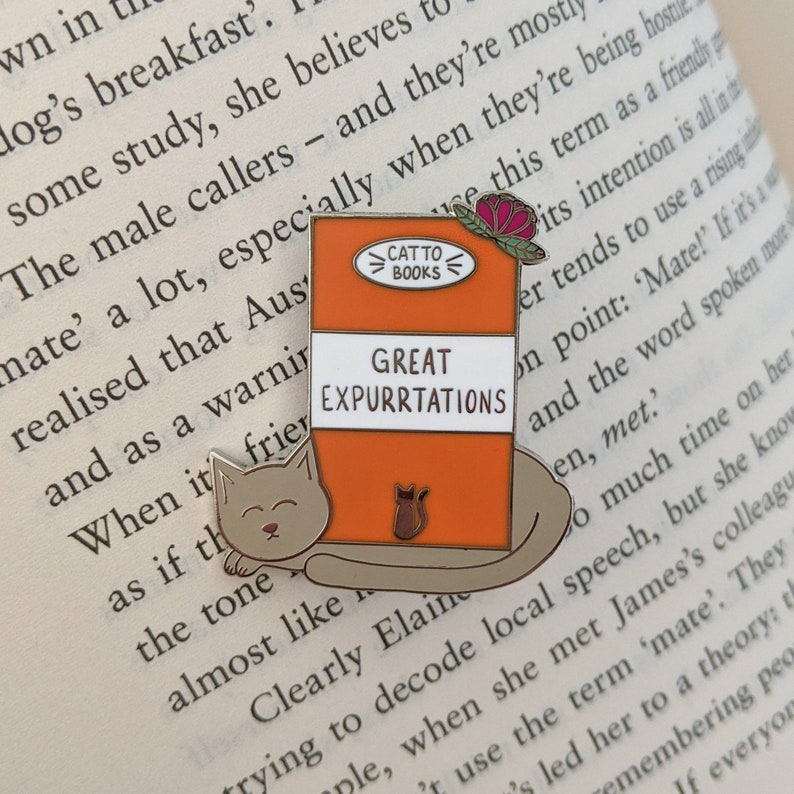 Cat Classics Enamel Pin that reads 'Great Expurrtations', photographed on an open book