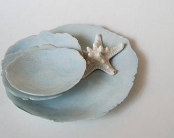 Handmade ceramic platters, set in light blue or creamy white