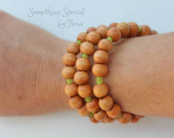 Wood beaded bracelet with frosted green feature beads, made on memory wire