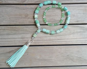 Long pale green suedette tassel necklace, with green wooden and white frosted beads