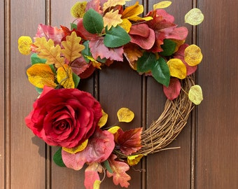 Autumn wreath with a red rose and yellow, orange and red foliage for indoor or outdoor use