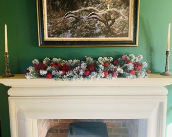 Small mantelpiece garland with fake snow and gold and maroon decorations