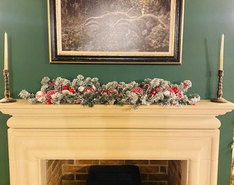 Red and white snowy Christmas garland with bells for mantelpiece or dining table decoration