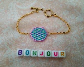 Women weaving brickstitch turquoise and pink bracelet