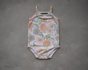Straped bodysuit in peach-flowered jersey on a white background