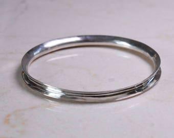 Handraised silver anticlastic wave bangle