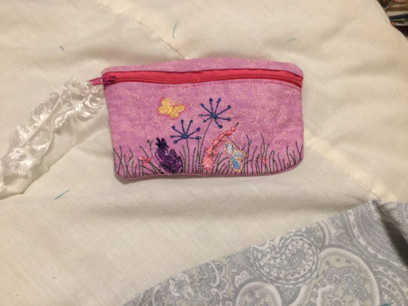 Pink in colored embroidered flowers with small Butterflies on it. 5.5  x 4.5 in size Embroidered bag