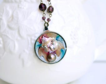 Small abstract floral peach and teal painted pendant with bedazzled chain with lilac, brown, and soft-colored-copper beads
