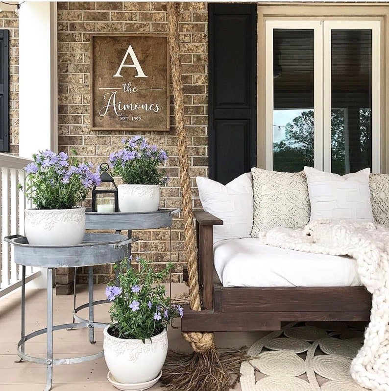 Rustic decor and personalized farmhouse sign on a beautiful porch with wood swing and galvanized accessories.