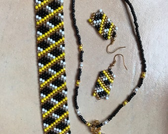 Diagonal plaid set in gold, silver, black, white and yellow.