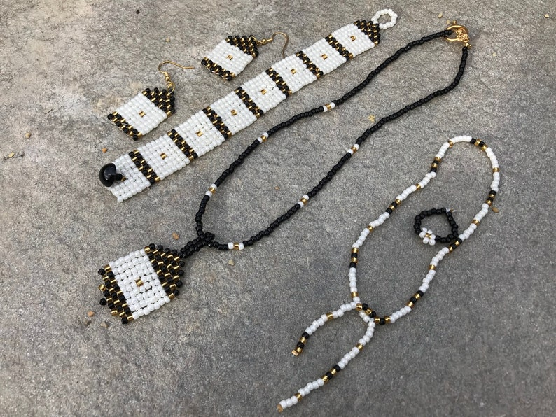 Eye catching seed bead set in pearl white box design separated by black and gold checkerboard.